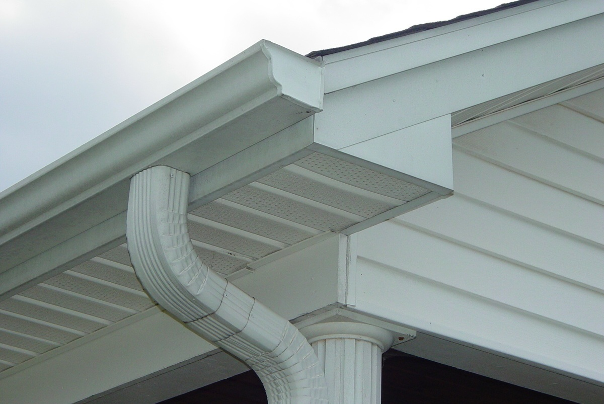 Seamless gutters installed on white house with downspout