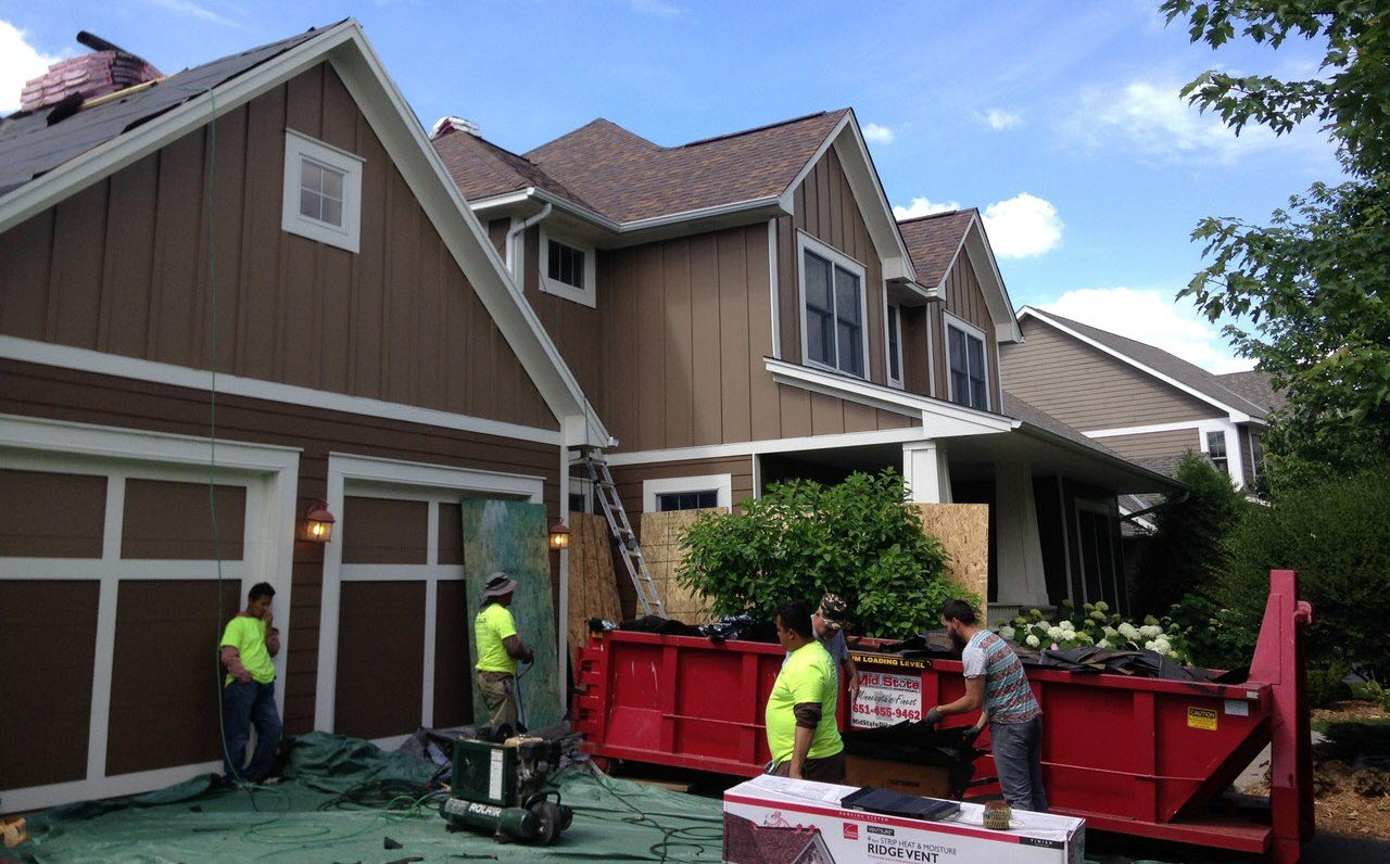 roofing contractors putting shingles and nails in a dumpster during roof repair process
