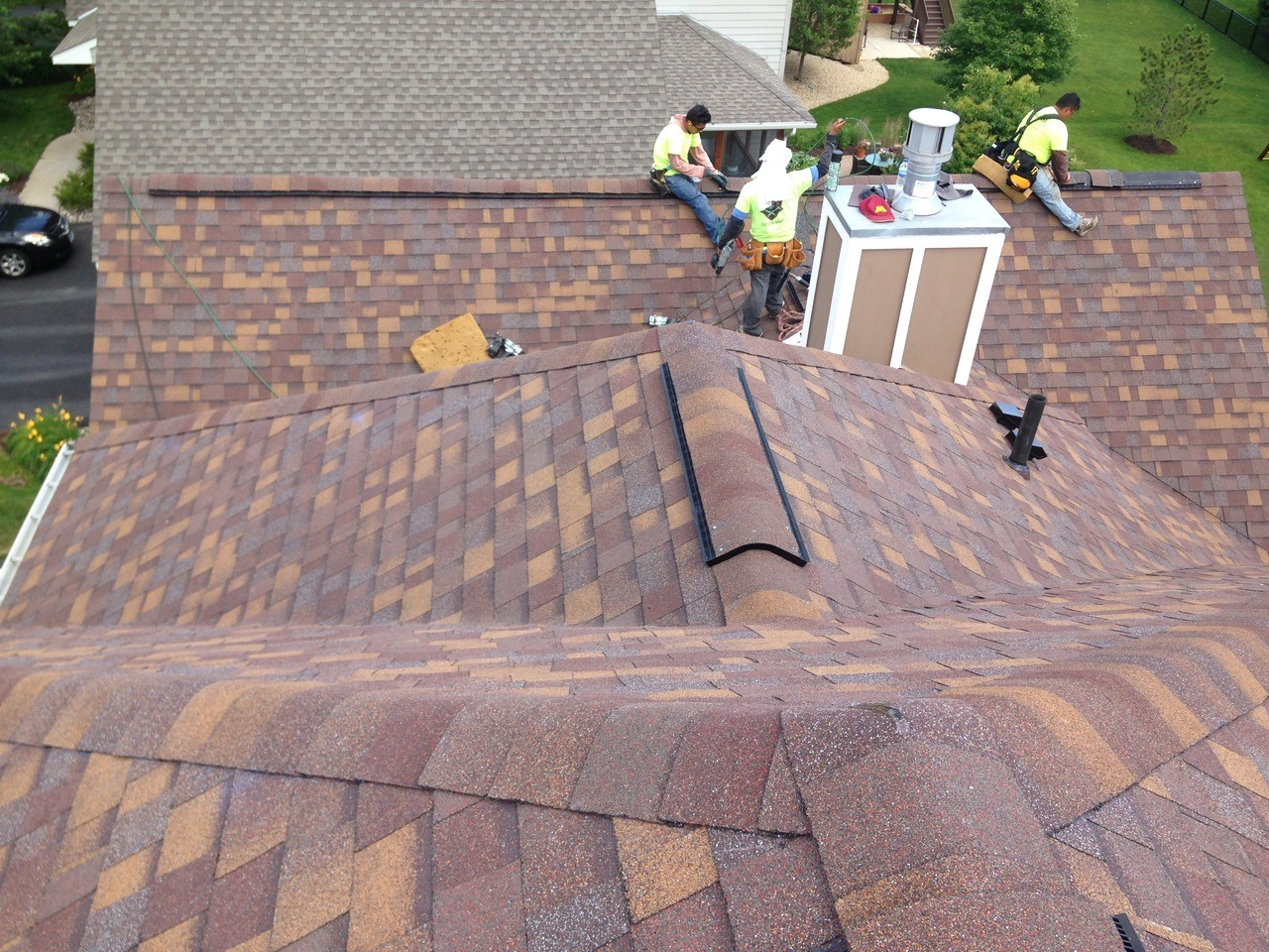 Construction company local crew on roof installing flashing on residential home