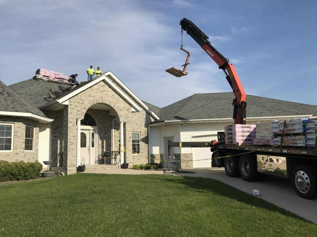 Maus Construction roofing crew receiving shingles for a roof replacement project