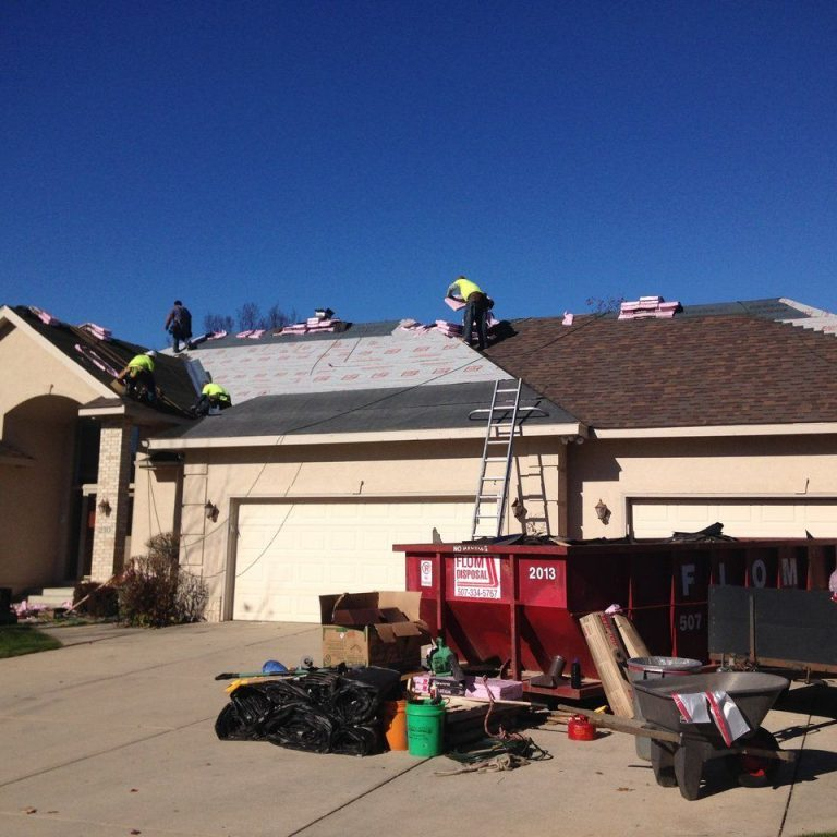 Roofers repairing roof after hail storm damage